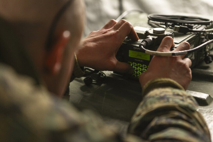 U.S. Marine Corps field radio operator sets up a PRC-117G field radio in preparation for an Air Base Ground Defense (ABGD) Field Exercise held Marine Corps Auxiliary Landing Field Bogue, N.C., on Feb. 24, 2015.