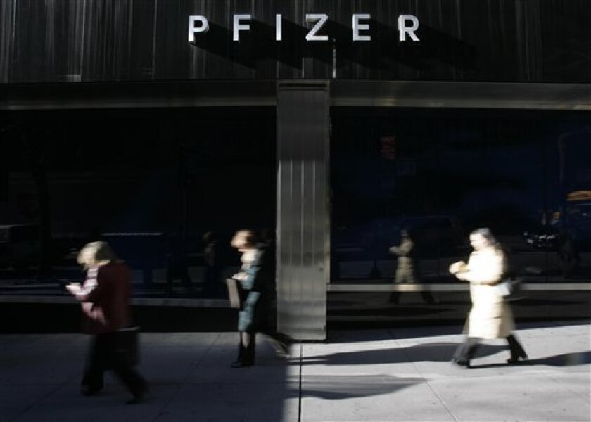 In this Dec. 4, 2006 file photo, pedestrians walk past Pfizer world headquarters in New York.  Drug giant Pfizer Inc. plans to lay off nearly a third of its 8,000 salespeople, according to published reports Friday, Jan. 16, 2009. (AP Photo/Seth Wenig, file)