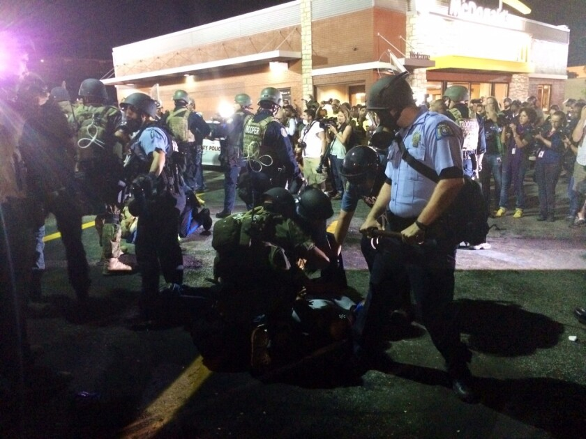 Police arrest a man in Ferguson, Mo., after someone threw a bottle.