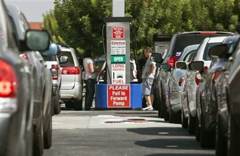 FILE - In this Friday, Oct. 5, 2012, file photo, Costco members fill up with discounted gasoline at a Costco gas station in Van Nuys, Calif.  U.S. oil output rose 14 percent to 6.5 million barrels per day in 2012,  a record increase, but you'd never know it from the price at the pump. The national