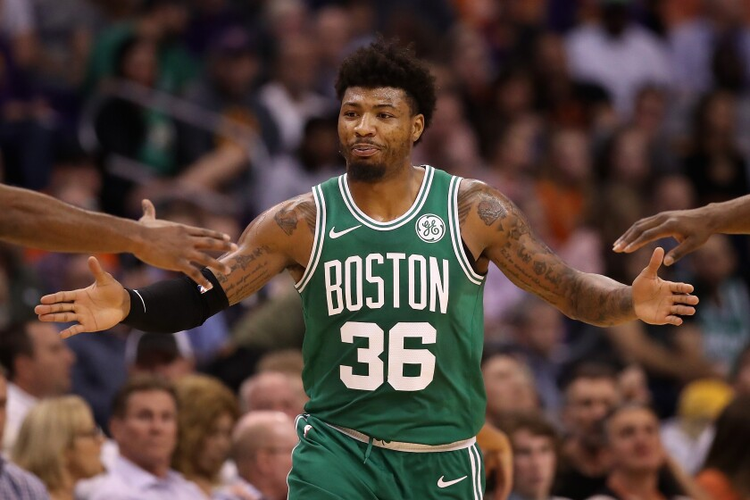 Celtics guard Marcus Smart gets high-fives from teammates during a break in play against the Suns on Nov. 18, 2019, in Phoenix.