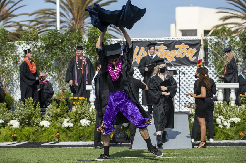 Logan Thobe tears off a pair of rip-away pants during Huntington Beach High School 2021 commencement ceremony.
