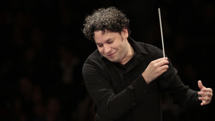 Gustavo Dudamel holds a baton in one hand and gestures with the other