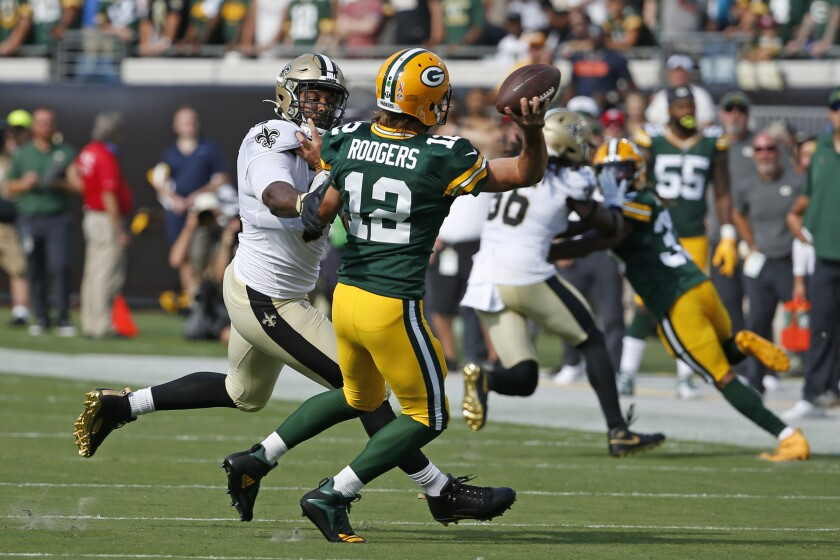 Green Bay Packers quarterback Aaron Rodgers (12) is his by New Orleans Saints defensive end Cameron Jordan, left, as he releases a pass during the first half of an NFL football game, Sunday, Sept. 12, 2021, in Jacksonville, Fla. (AP Photo/Stephen B. Morton)