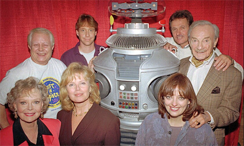 "The crew from the original cast of the television series ""Lost in Space"" pose with the show's robot in in a 1995 file photo. From left in the back row are: Bob May, Bill Mumy, Mark Goddard, Jonathan Harris; in the front row from left: June Lockhart, Marta Kristen, Angela Cartwright."