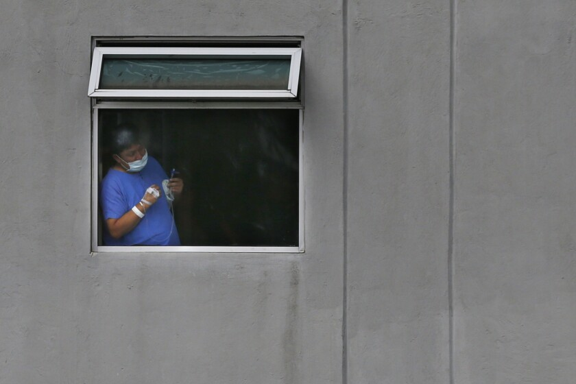 Wearing a mask to curb the spread of the new coronavirus, a patient looks out of a window at the Ignacio Zaragoza general hospital in the Iztapalapa borough of Mexico City, Monday, August 9, 2021. Mexico will ask the United States to send at least 3.5 million more doses of COVID-19 vaccine as the country faces a third wave of infections, President Andres Manuel Lopez Obrador said Monday. (AP Photo/Marco Ugarte)