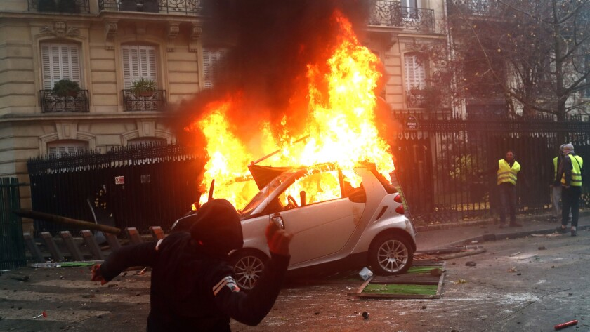 A hooded demonstrator throws something as a car burns Saturday during a protest in Paris.