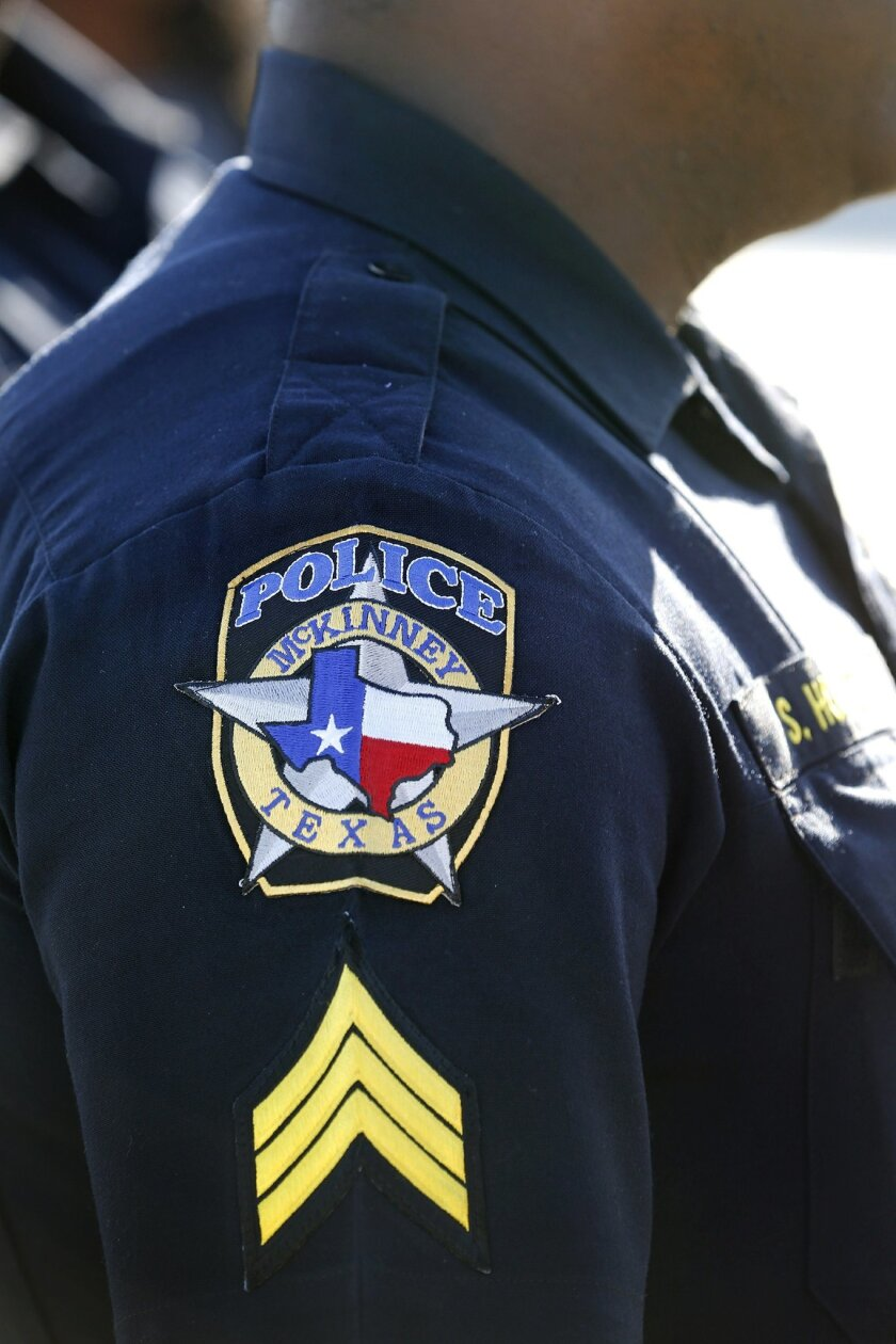 In this June 8, 2015 photo, a McKinney police officer stands near demonstrators during a protest in response to an incident at a community pool involving local police officers in McKinney, Texas. McKinney is an affluent Dallas suburb that is among the nation's fastest-growing cities, with highly re