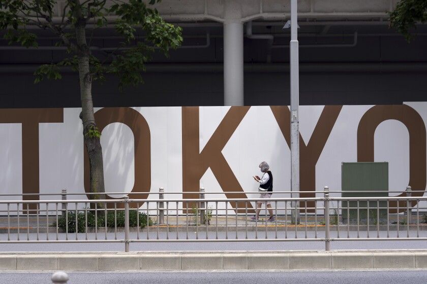 A person walks next to the National Stadium, where opening ceremony and many other events are scheduled for the postponed Tokyo 2020 Olympics, Wednesday, June 2, 2021, in Tokyo. Roads are being closed off around Tokyo Olympic venues including the new $1.4 billion National Stadium where the opening ceremony is set for July 23.(AP Photo/Eugene Hoshiko)