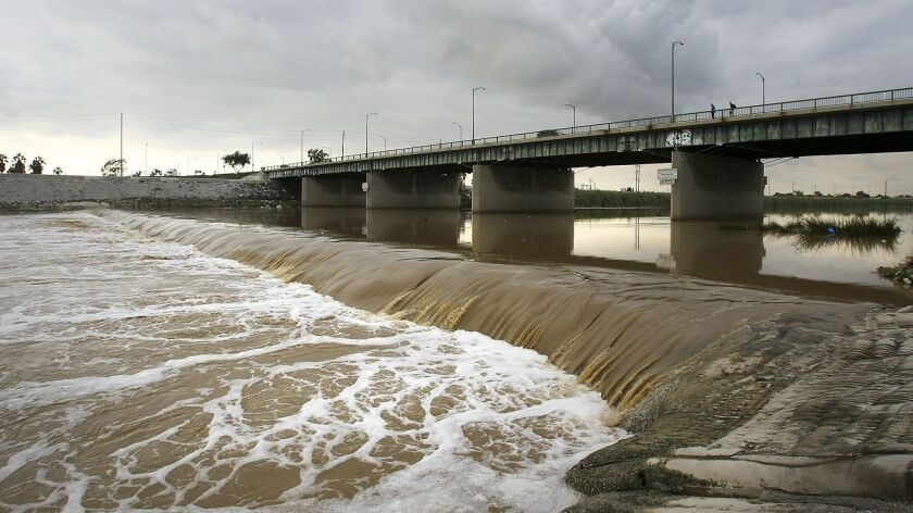 A stormwater-swollen Los Angeles River flows under the Anaheim Street bridge in Long Beach on its way to the Pacific Ocean.