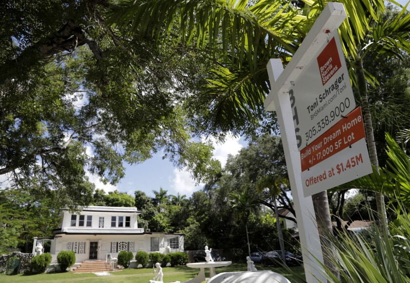 FILE - In this July 22, 2019 file photo, a for sale sign is posted in front of a home in Miami. In this first few months after the new federal tax law went into effect, Florida saw jumps in new residents moving from Connecticut and Massachusetts. New figures released Thursday, Oct. 31, 2019, by the U.S. Census Bureau offer a glimpse of the impact of the 2017 tax law on U.S. migration patterns from high-tax northeastern states to Florida, which doesn't have a state income tax and has low property taxes (AP Photo/Lynne Sladky, File)