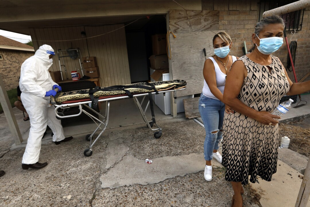 Juan Lopez wheels a gurney up to the home of Amalia Tinoco, 91, who died after becoming infected with COVID.