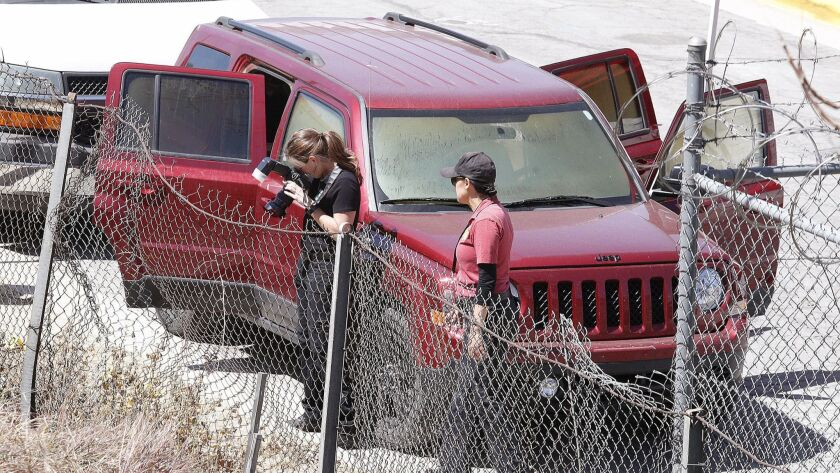 Police investigators examine the scene on South Varney Street near Linden Court in Burbank where three bodies were found in a burgundy Jeep Patriot.