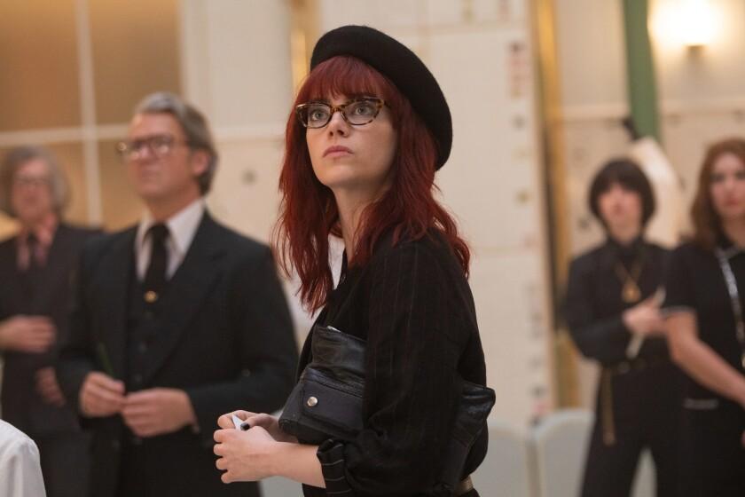 "Emma Stone, in red hair and beret, in ""Cruella."""