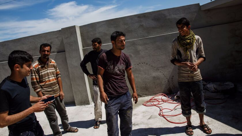 Raed Mohammed Hasan, center, recounts the Jan. 17 airstrike that he said killed 11 people in his hom