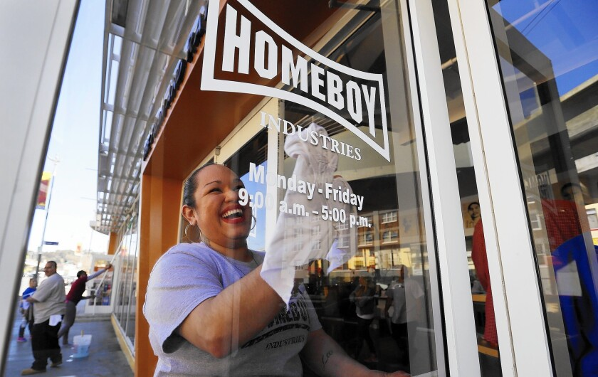 Homeboy Industries is planning to expand into a building next door to its current headquarters in Chinatown, where Ilenee Velasco cleans the front windows.