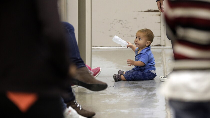 A toddler sits on the floor at a U.S. Customs and Border Protection processing facility in Brownsville, Texas.