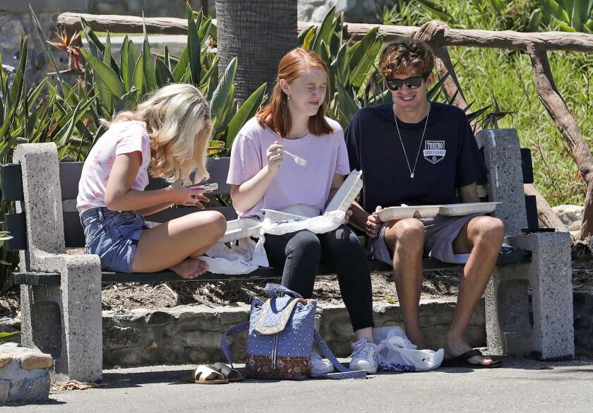 Three teens have lunch at Heisler Park in Laguna Beach on Thursday.