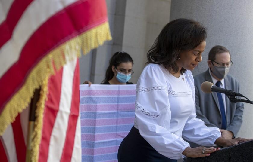 Capri Maddox prays at city hall event.
