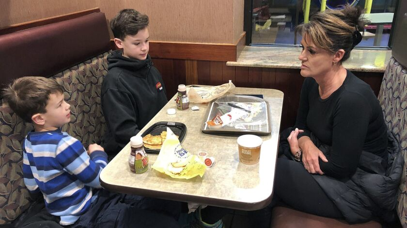In this Jan. 10, 2019, photo, Tamra Cartwright talks with sons Connor, 7, left, and Caden, 11, about the effect of multiple aftershocks from Alaska's recent magnitude 7 earthquake.