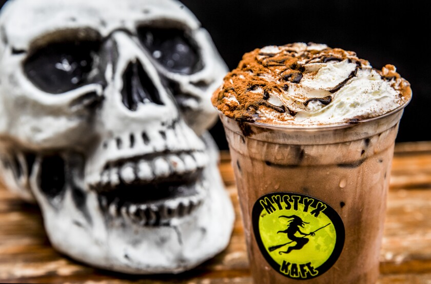 A skull sits next to a mocha drink.