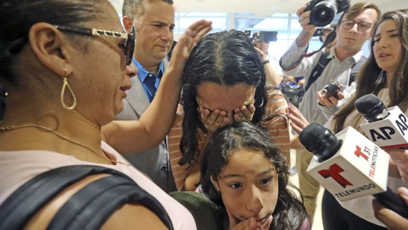 Alejandra Juarez, 39, left, says goodbye to her children, Pamela and Estela on Friday at the Orlando, Fla., airport.