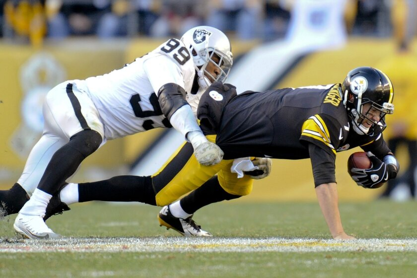 Pittsburgh Steelers quarterback Ben Roethlisberger (7) is injured as he is tackled by Oakland Raiders outside linebacker Aldon Smith (99) in the fourth quarter of an NFL football game Sunday, Nov. 8, 2015, in Pittsburgh. The Steelers won 38-35. (AP Photo/Don Wright)