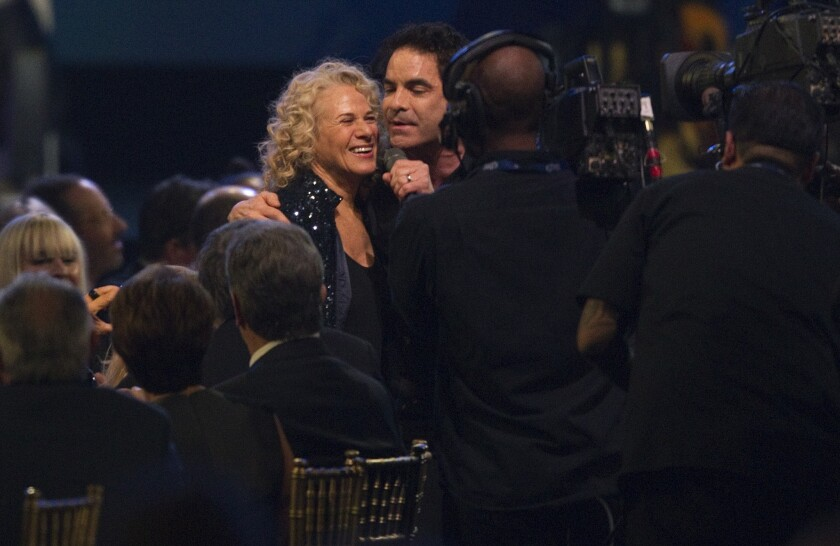 Pat Monahan grasps the shoulder of Carole King in the audience while singing one of her songs during the MusiCares Person of the Year concert honoring King.