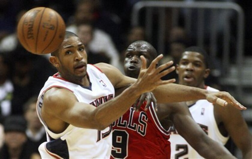 Atlanta Hawks center Al Horford, left, loses control of the ball as Chicago Bulls forward Luol Deng (9) defends during the first half of an NBA basketball game, Friday, Feb. 5, 2010, in Atlanta. (AP Photo/John Amis)