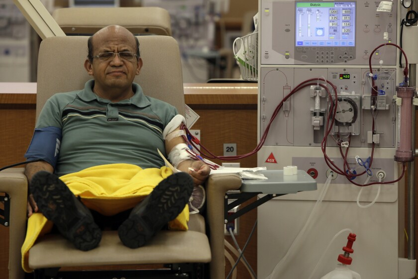 Giraldo Garcia, with feet up and eyes closed, receives dialysis treatment.
