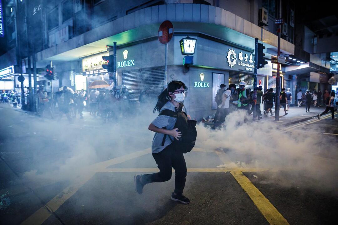 A woman runs through tear gas on a city street