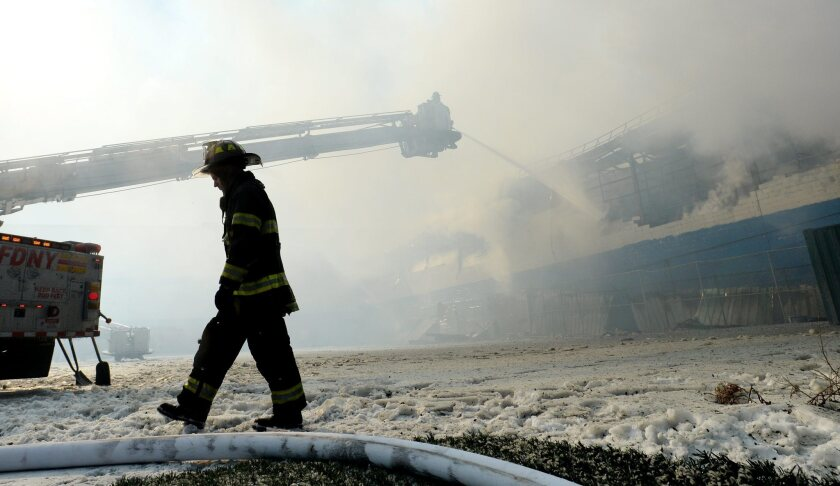 Firefighters work to extinguish a large warehouse fire in Brooklyn, N.Y.