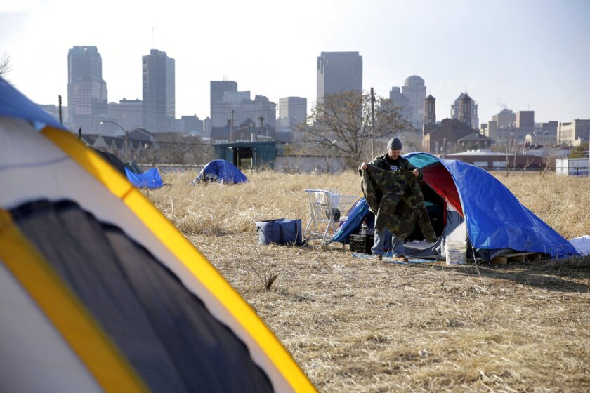 A man cleans out his tent at a homeless encampment near downtown St. Louis in 2015.
