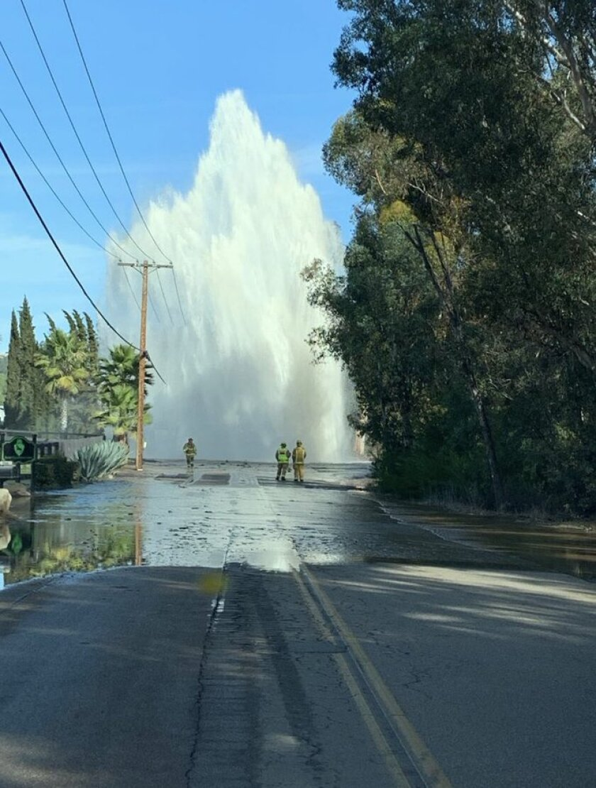San Marcos firefighters assess a water main break on North Twin Oaks Road on Saturday.