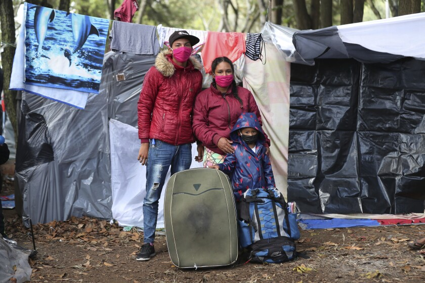 Maicol Hernandez, left, and his wife Railin Hernandez pose with their son Elieker Hernandez outside their tent in a park where they have been living with other jobless Venezuelan migrants since the end of May, near the bus station in Bogota, Colombia, Wednesday, June 10, 2020. The former motorcycle mechanic and housewife left their native Merida two years ago when they traveled on foot to Lima, Peru, where he worked at a restaurant and fruit store. When the lockdown to contain the COVID-19 pandemic left Hernandez without work, they again walked, this time to Bogota, where they are waiting to be tested for COVID-19 in order to be allowed back into Venezuela, and amid long-distance travel restrictions within Colombia. (AP Photo/Fernando Vergara)