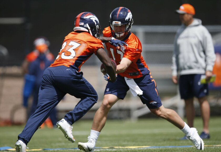 Denver Broncos quarterback Trevor Siemian, right, hands off the ball to running back Ronnie Hillman during NFL football practice Tuesday, May 31, 2016, at the team's headquarters in Englewood, Colo. (AP Photo/David Zalubowski)