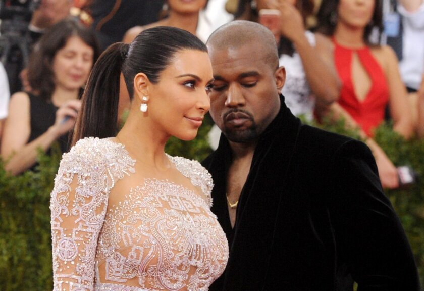 FILE - In this May 4, 2015, file photo, Kim Kardashian, left, and Kanye West arrive at The Metropolitan Museum of Art's Costume Institute benefit gala in New York. Kardashian posted a tribute to West on Instagram to mark the couple's second wedding anniversary on May 24, 2016. (Photo by Charles Sykes/Invision/AP, File)