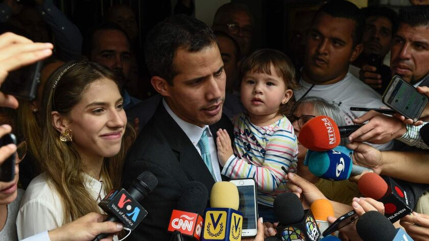 Opposition leader and self-proclaimed interim president Juan Guaido talks to the press as he holds his daughter, Miranda, while standing next to his wife, Fabiana, outside their home Thursday.