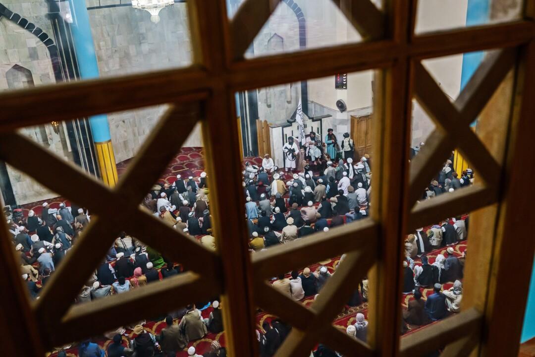 Men at a religious service are seen through wooden lattice work.