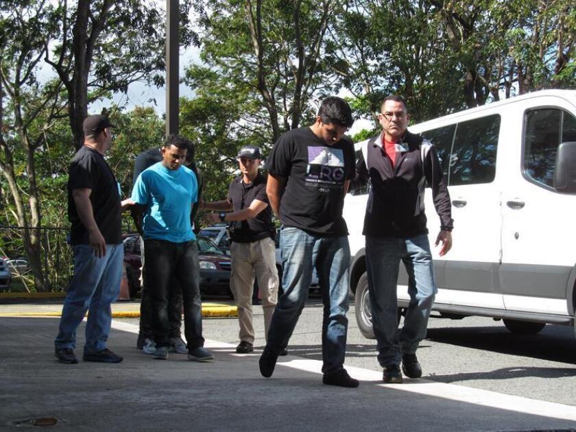 Un grupo de policías escolta el lunes 11 de enero de 2016 a algunas de las mas de 160 personas detenidas en lo que ha marcado el mayor operativo de la historia de Puerto Rico en materia de tráfico ilegal de armas. EFE/Archivo