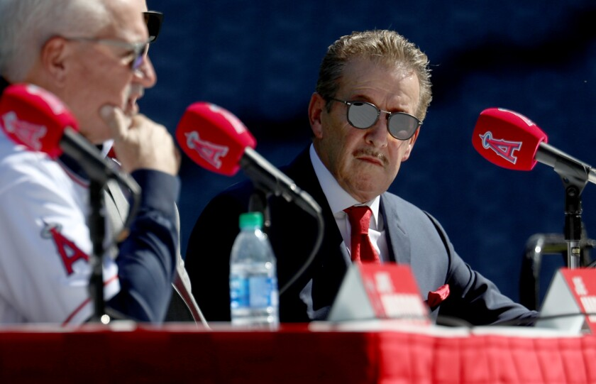 Angels owner Arte Moreno looks on as Joe Maddon speaks to reporters during his introductory news conference
