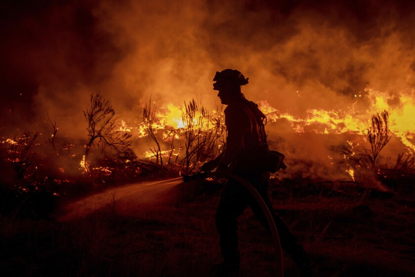 A firefighter hoses down flames amid a wildfire.