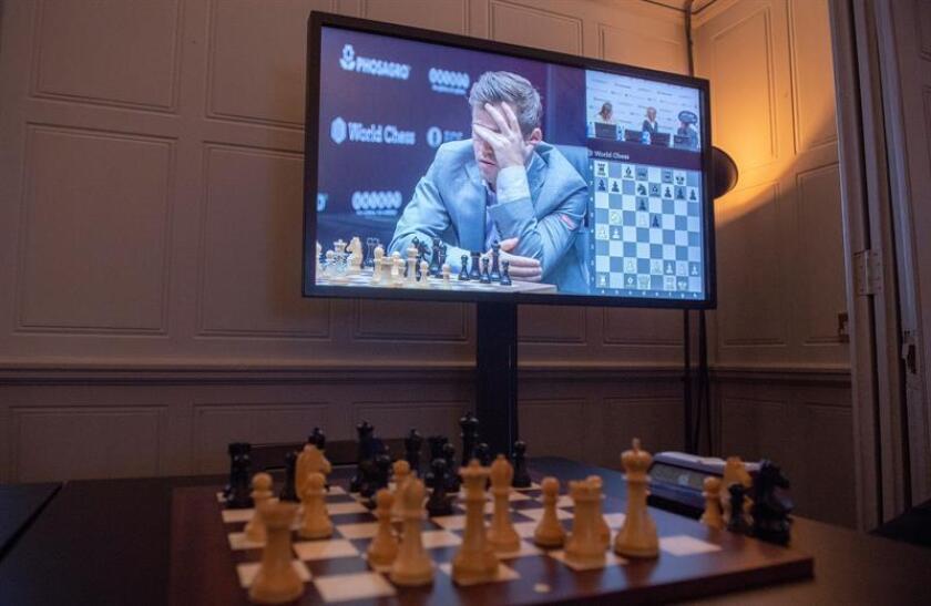 Una pantalla de televisión muestra en vivo al Campeón Mundial de Ajedrez de Noruega Magnus Carlsen jugando contra el retador estadounidense Fabiano Caruana en el juego de la Ronda 10 durante el Campeonato Mundial de Ajedrez 2018 en Londres, Gran Bretaña, 22 de noviembre de 2018. EFE/Archivo