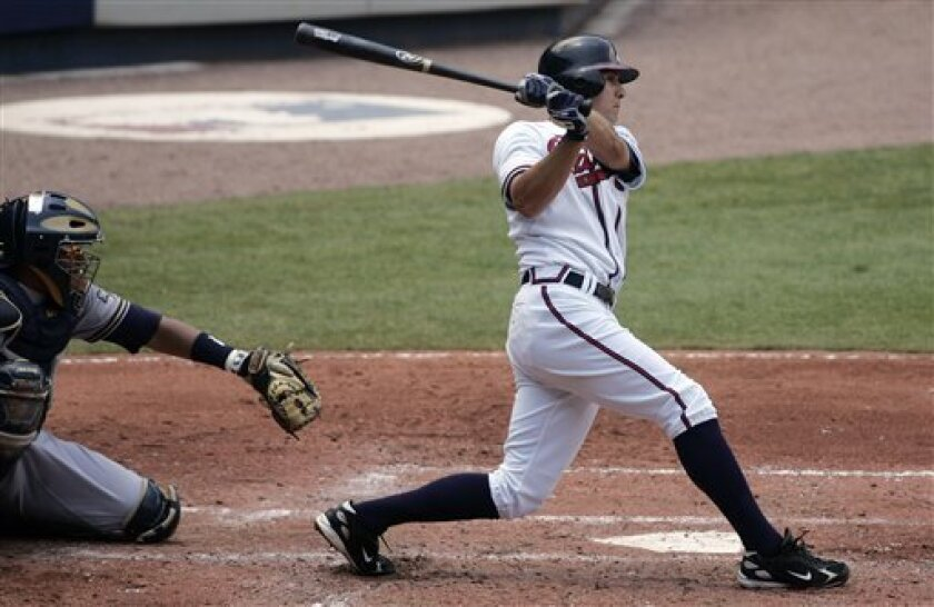 Atlanta Braves' Kelly Johnson connects for a two-run double as Milwaukee Brewers catcher Mike Rivera looks on in the third inning of a baseball game in Atlanta Wednesday, June 25, 2008. . (AP Photo/John Bazemore)