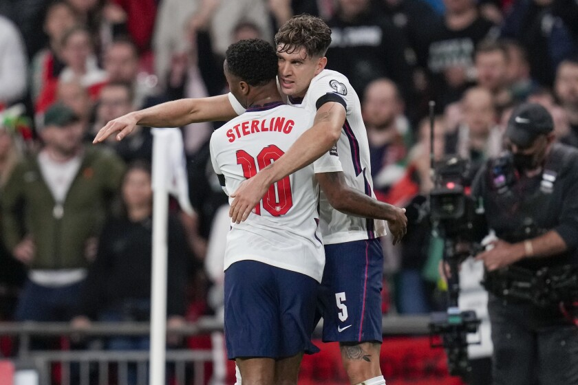 England's John Stones, right, is congratulated by teammate Raheem Sterling after scoring his team's first goal during the World Cup 2022 group I qualifying soccer match between England and Hungary at Wembley stadium in London, Tuesday, Oct. 12, 2021. (AP Photo/Kirsty Wigglesworth)