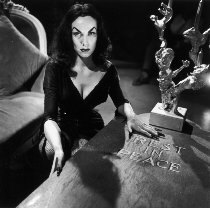 A publicity photo of actress and TV host Vampira, real name Maila Nurmi, crouching beside a wooden coffin, circa 1956.