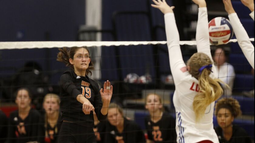 Huntington Beach High's Sabrina Phinizy (19) scores against Los Alamitos during the second set in a