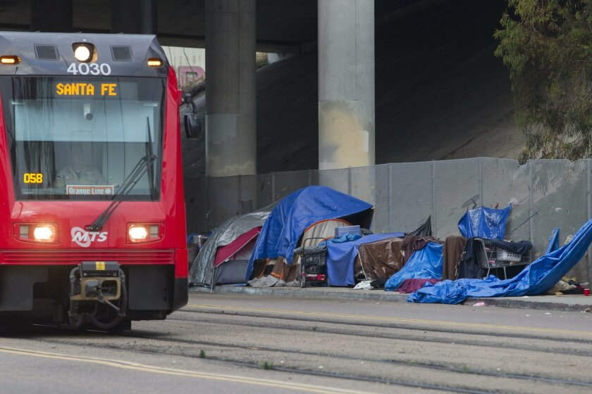 In this 2015 file photo, homeless people along Commercial Street downtown set up makeshift tents before the sun sets.