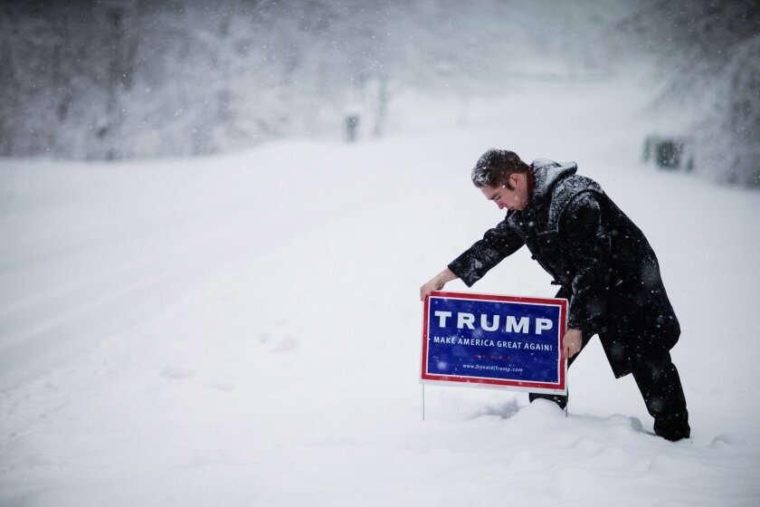 James Radcliffe, a volunteer for Republican presidential candidate Donald Trump, places a sign outside a home while walking through the snow knocking on doors in search of Trump supporters Friday, Feb. 5, 2016, in Londonderry, N.H.  (AP Photo/David Goldman)