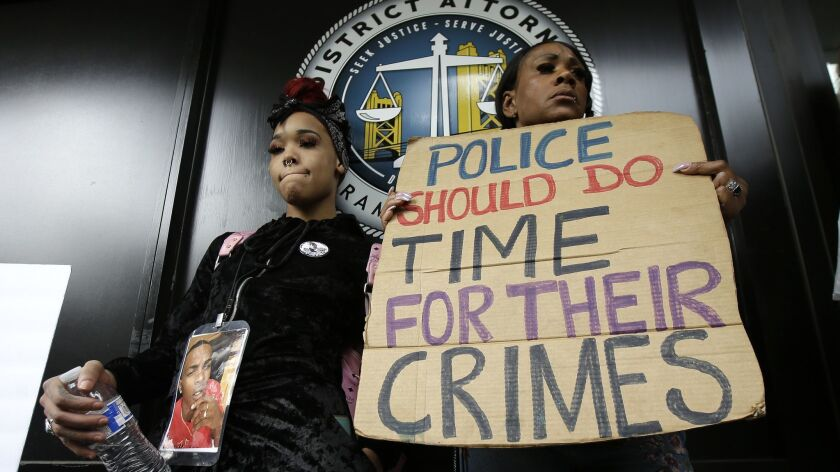 In this April 4, 2018 file photo protesters stand outside the office of Sacramento County Di